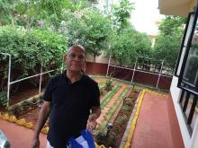 Mr Balagopal in a black t-shirt in front of the garden he loves to work in